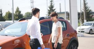 O serviço do carro, gerente novo do carro está o automóvel seguinte e discute algo com o cliente que fêmea fala o mecânico e vídeos de arquivo