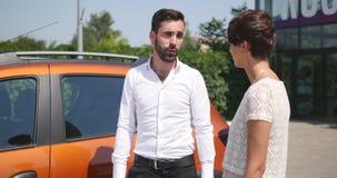 O serviço do carro, gerente novo do carro está o automóvel seguinte e discute algo com o cliente que fêmea fala o mecânico e video estoque