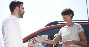 O serviço do carro, gerente novo do carro está o automóvel seguinte e discute algo com o cliente que fêmea fala o mecânico e filme