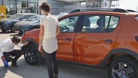 O serviço do carro, mecânico novo está o automóvel seguinte e discute algo com o cliente que fêmea fala o mecânico e Imagens de Stock Royalty Free