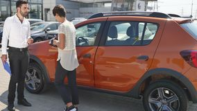 O serviço do carro, mecânico novo está o automóvel seguinte e discute algo com o cliente que fêmea fala o mecânico e Fotos de Stock