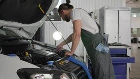 O serviço do carro, mecânico que trabalha na oficina, ferramenta profissional no mechanician das mãos, especialista novo repara o vídeos de arquivo