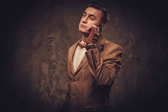 O Sharp vestiu o homem com o revestimento e laço vestindo do telefone celular Fotografia de Stock