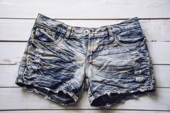 O short das calças de brim é colocado no assoalho de madeira branco imagem de stock royalty free