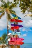 O sinal colorido aponta a maneira aos destinos diferentes no th Fotografia de Stock