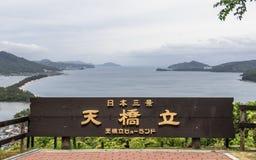 O sinal com rotulação de Amanohashidate, em engl 'Céu Brigde, herança de Japão 'com baía e ilhas de Miyazu entre um gre fotografia de stock royalty free