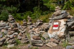 O sinal da fuga de caminhada marca pintado em uma rocha na pilha de pedras do zen Calha principal do trajeto Forest National Park fotografia de stock
