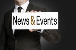O sinal da notícia e dos eventos é mantido pelo homem de negócios Imagens de Stock Royalty Free