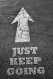 O sinal da seta na superfície do asfalto com mantém-se ir Fotos de Stock Royalty Free