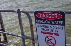 O sinal de aviso 'água pouco profunda do perigo que salta e que mergulha proibida 'em um molhe fotografia de stock