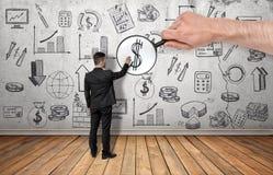 O sinal de dólar tocante do homem de negócios ampliado pela lente de aumento na equipa a mão Imagens de Stock