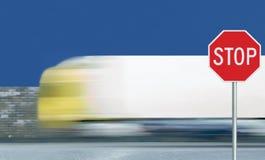 O sinal de estrada vermelho da parada, fundo borrado movimento do tráfego de veículo do caminhão, leva octógono de advertência re imagens de stock