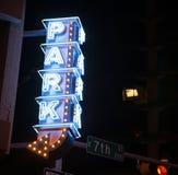 O sinal de néon azul empilhado verticalmente diz o parque aqui foto de stock royalty free