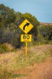 O sinal de rua em Austrália que adverte a curva direita adiante apressa 80 na terra seca imagens de stock
