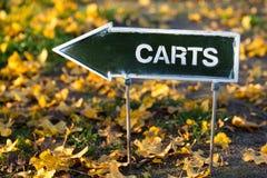 O sinal de sentido dos carrinhos de golfe no campo do golfe do outono Fotografia de Stock