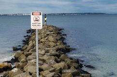 O sinal de tráfego para a atividade do risco elevado, evita a parede litoral rochosa do oceano foto de stock