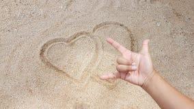 O sinal do coração estava escrevendo na areia amarela Foto de Stock
