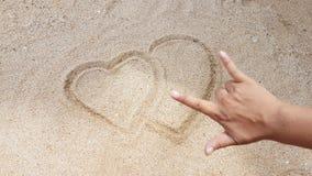 O sinal do coração estava escrevendo na areia amarela Fotos de Stock