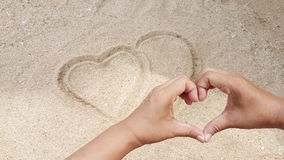 O sinal do coração estava escrevendo na areia amarela com sinal do amor da mão Imagem de Stock