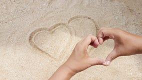 O sinal do coração estava escrevendo na areia amarela com sinal do amor da mão Fotografia de Stock Royalty Free