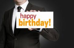 O sinal do feliz aniversario é mantido pelo homem de negócios Foto de Stock