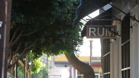 O sinal do rum pendura sob um toldo azul e umas árvores verdes em Windy Day vídeos de arquivo