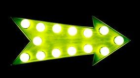 O sinal metálico iluminado brilhante e colorido do vintage verde da exposição da seta com as ampolas de incandescência isolou o f fotografia de stock