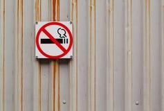 O sinal n?o fumadores pendura em uma superf?cie de metal cinzenta oxidada imagens de stock royalty free