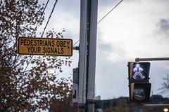 O sinal pedestre que indica os pedestres pode andar ao lado de um sinal que pedem que os povos respeitem o c?digo e o sinal imagem de stock royalty free