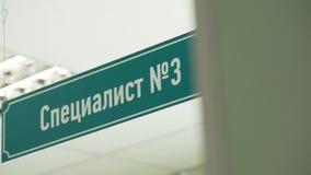 O sinal plástico verde sob o teto com texto cirílico diz o especialista número três vídeos de arquivo