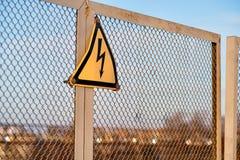 O sinal que adverte sobre o perigo da eletricidade em uma cerca do metal Imagens de Stock