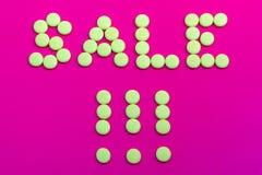 O sinal relativo à promoção vestiu-se com doces amarelos em um backgroun cor-de-rosa Imagem de Stock