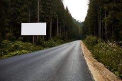 O sinal vazio do quadro de avisos pela estrada vazia através das montanhas da floresta ajardina Painel do anúncio na estrada Imagem de Stock