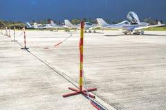 O sinal vermelho e amarelo do polo com uma corrente proibe povos da passagem em um aeroporto imagem de stock