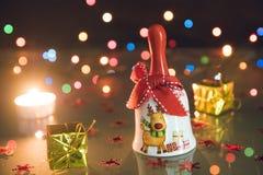 O sino de Natal, os presentes pequenos e as velas claras do chá no bokeh enegrecem o backgound Imagens de Stock Royalty Free