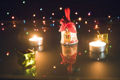 O sino de Natal, os presentes pequenos e as velas claras do chá no bokeh enegrecem o backgound Fotografia de Stock Royalty Free
