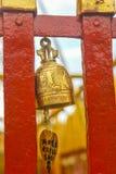 O sino dourado suspendeu em um quadro pintado vermelho Fotos de Stock Royalty Free