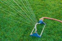 O sistema de extinção de incêndios do gramado pulveriza a água sobre a grama verde fotografia de stock royalty free