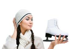 O skater de figura fêmea olha o patim Foto de Stock