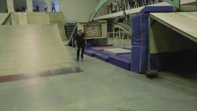O skater do rolo faz a competência para fazer conluios no trampolim Passatempo extremo Competição no skatepark video estoque
