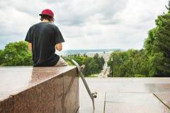 O skater senta com a sua a parte traseira e pensa ao lado do skate fotografia de stock