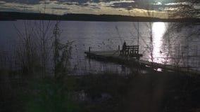 O slider disparou de um assento da menina em um banco na plataforma de madeira pelo lago durante o tempo do por do sol filme