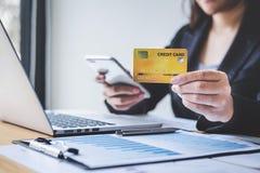O smartphone da terra arrendada do consumidor de mulher do negócio, o cartão de crédito e a datilografia no portátil para a compr fotografia de stock