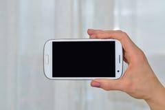 O smartphone em sua mão Imagens de Stock