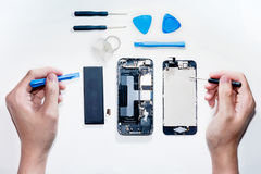 O smartphone era os danos e a necessidade reparar que utiliza ferramentas o smartphone que está no fundo branco imagens de stock