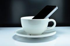 O smartphone está na caneca de café O conceito li alguns povos Imagens de Stock