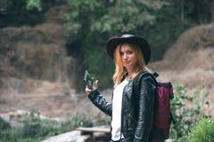 O smartphone fêmea do uso do turista, com a trouxa e o chapéu de vaqueiro que olham o rio lavou afastado a ponte, o cruzamento er fotos de stock royalty free