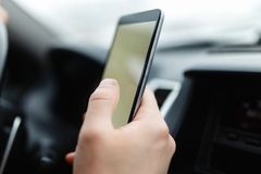 O smartphone moderno com a tela vazia com espaço da cópia para seu texto ou projeto, close-up do motorista masculino entrega usan imagens de stock