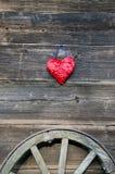 O símbolo vermelho do coração na parede de madeira velha do bartn e o transporte rodam Imagens de Stock
