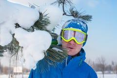 O snowboarder alegre em óculos de proteção do sol está estando ao lado com neve Foto de Stock